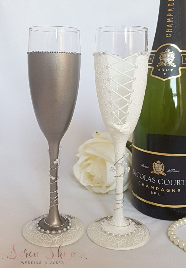 Wedding champagne flutes for the bride and groom to match their outfits and personalised with names and date.