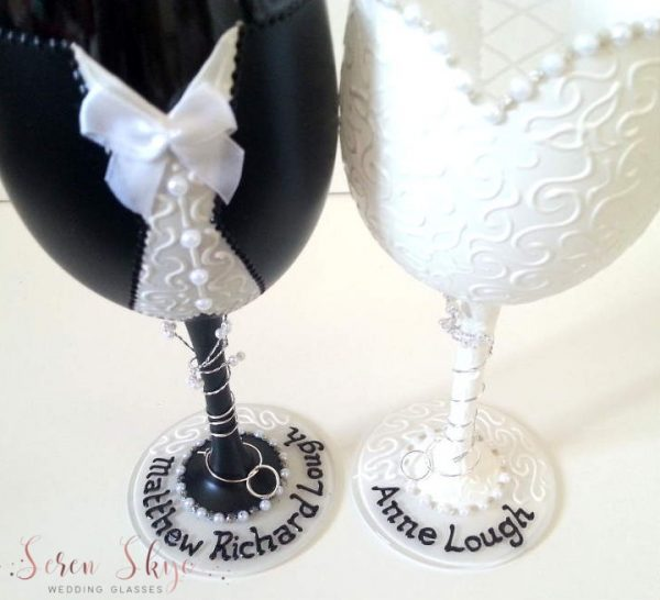 A pair of black and white wedding wine glasses hand painted and personalised with names around the base.
