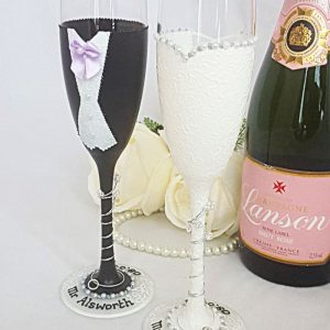 Bride and groom champagne flutes with black jacket and lilac bow tie, personalised with the couple's names and date around the bases.