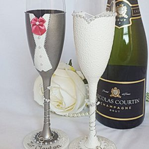 A pair of personalised and hand painted champagne flutes for a wedding gift, painted to match the groom's suit colour and with names and wedding date.