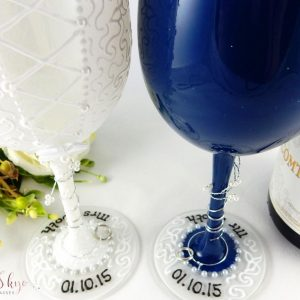 A pair of personalised wedding wine glasses with the bride and groom's names and dates written on the bases.