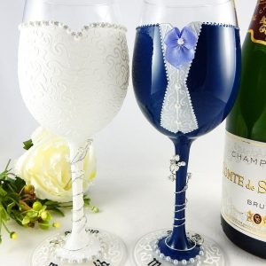 Hand painted wedding wine glasses for the bride and groom with names and wedding day written on the bases in black writing.