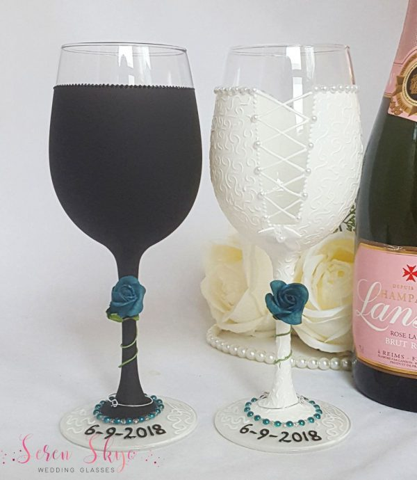The back of some personalised wedding wine glasses hand painted to match outfits, and with a teal rose winding around the stem.