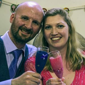 Bride and groom holding bespoke wedding champagne flutes to match their outfits.