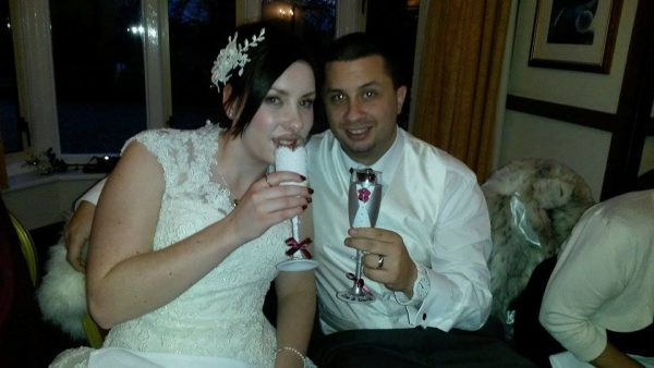 Newlyweds with hand painted champagne flutes on their wedding day with burgandy colour scheme.