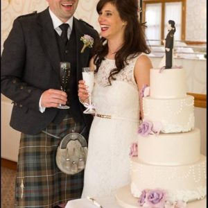 Bride and groom with personalised tartan champagne flutes on their wedding day.
