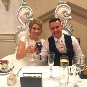 Bride and groom with hand painted bespoke champagne glasses with Catherine Parry wedding dress.
