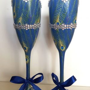 Bespoke bridesmaids champagne glasses with peacock pattern and diamante belt.