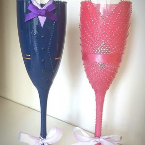 Bespoke wedding champagne flutes with coral dress and blue suit.