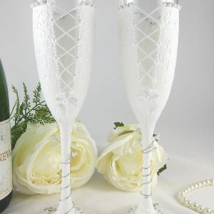 The backs of a set of Mrs & Mrs champagne flutes for a same sex marriage gift.