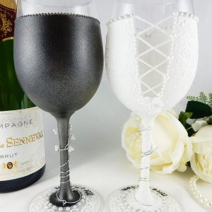 The backs of a set of wedding wine glasses to match the bride and groom's outfits.