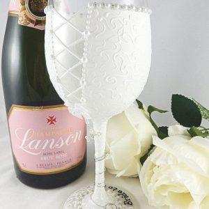 The back of a white bride to be wine glass with lace-up back and textured pattern.