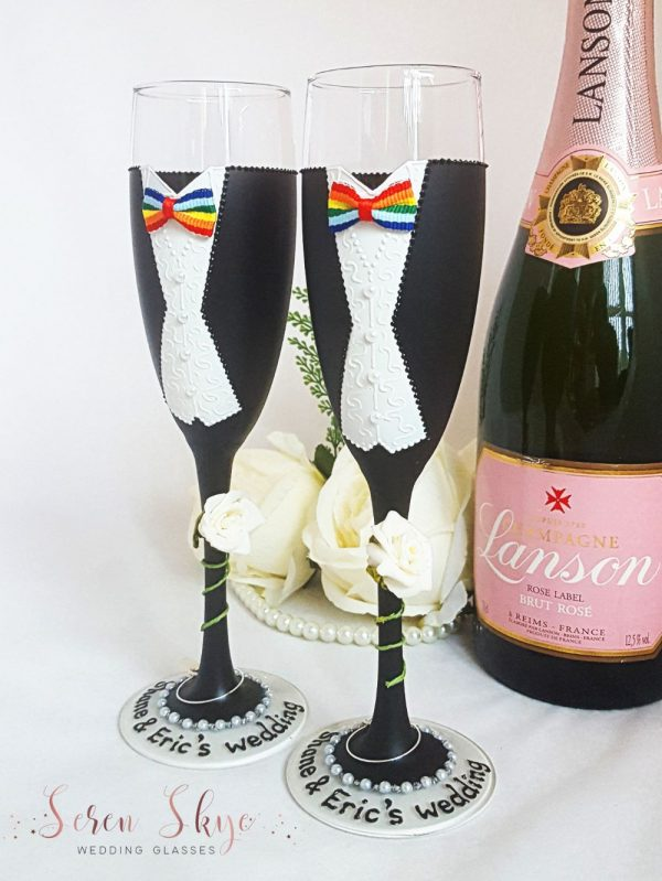 Same sex wedding champagne glasses with ivory roses and rainbow bows.