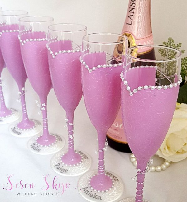 Hand painted bridesmaids champagne glasses for a lilac themed wedding.