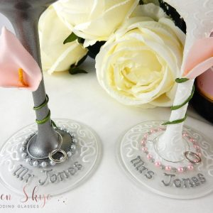 Wedding wine glass bases with silver writing and blush pink calia lilies.
