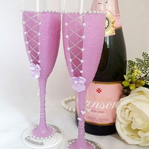 Two bridesmaids champagne flutes with lace-up back and personalisation on the bases.