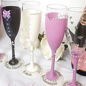 A set of champagne flutes for bridal party thank you gifts with names and date on the bases.