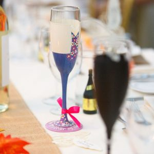 Custom hand painted mother of the bride champagne glass with blue dress and cream jacket.