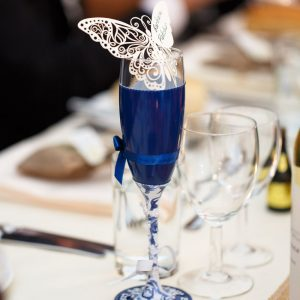 Bespoke hand painted champagne flute for the mother of the bride with floral dress and navy jacket.