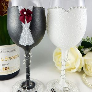 Bride and groom wine glasses with personalised bases, charcoal suit and burgandy bow tie.