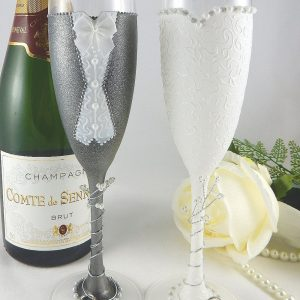 Wedding champagne glasses to match outfits with grey suit and pearl decoration.