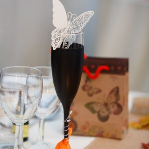 Groom's champagne flute with butterfly decoration on the top table.