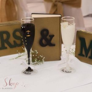 Uniform bride and groom champagne glasses.