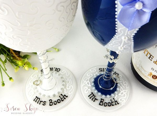 Bride and groom navy wedding wine glasses with names written on the bases.