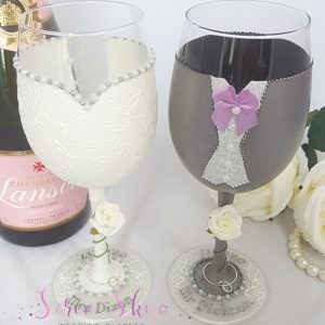 Personalised wedding wine glasses for the bride and groom with grey jacket and lilac bow tie, complete with ivory roses and names on the bases.