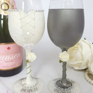 The backs of a pair of personalised wedding wine glasses with ivory roses.
