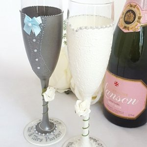 Personalised wedding champagne glasses for the newlyweds with a grey suit and waistcoat, pale blue bow tie and ivory roses.