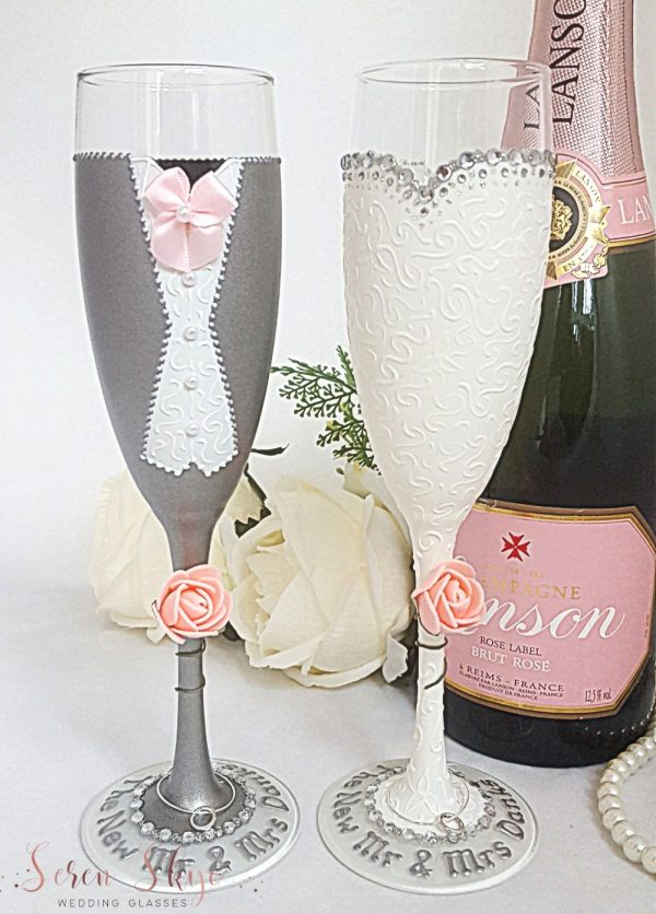 Personalised champagne flutes for the bride and groom, hand painted with a grey suit and diamante detail on the wedding dress, complete with names around the bases.