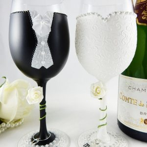 Black and white wedding wine glasses for the bride and groom with ivory roses winding around the stems.