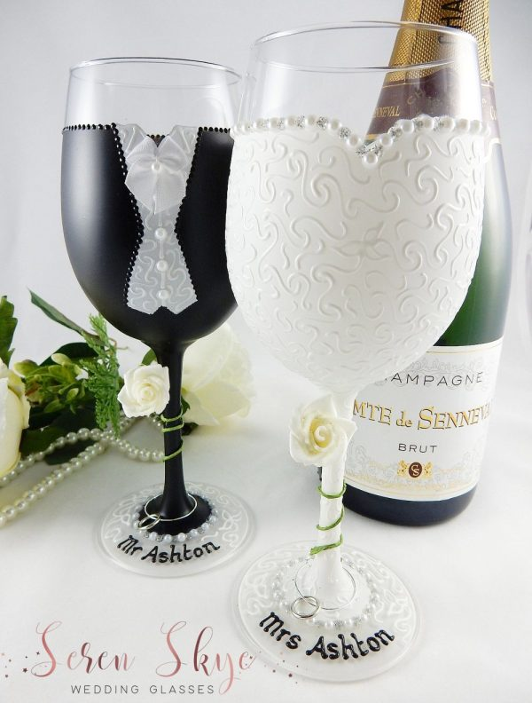 Bride and groom wine glasses with black suit and white dress.