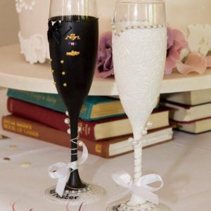 Bespoke wedding champagne flutes hand painted to match the bride and groom's outfits.
