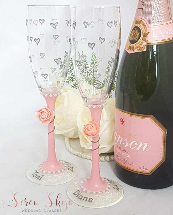 Blush pink wedding champagne flutes with little silver hearts